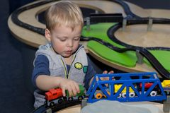Cute toddler playing with a toy train in children center royalty free stock photo