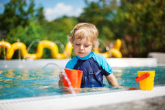 Cute toddler playing with water by the outdoor swimming pool Stock Image