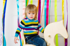 Cute toddler riding wooden hand crafted horse Stock Images