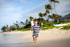 Cute toddler running on a tropical beach Stock Photo