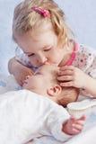 Cute Toddler sister kisses newborn Stock Images