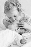 Cute Toddler sister kisses newborn Royalty Free Stock Photo