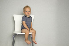 Cute toddler sitting on the chair against gray wall and looking at camera. Copy spase Royalty Free Stock Images