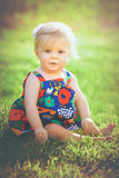 Cute toddler sitting in flowered dress stock photos
