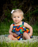 Cute toddler sitting in flowered dress royalty free stock photos