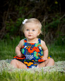 Cute toddler sitting in flowered dress Stock Image