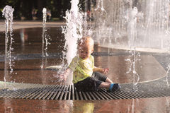Cute toddler sitting in fountain. Awesome baby boy having fun and plaing in fountain. Royalty Free Stock Photo
