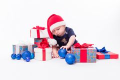 Cute toddler is sitting in a New Year`s cap among Christmas toys Royalty Free Stock Photography