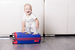 Cute toddler sitting on the suitcase and looking at camera. Funny baby boy going to vacation. Royalty Free Stock Photo
