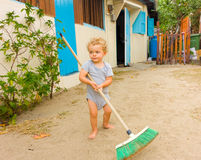 A cute toddler sweeping a yard in the caribbean Stock Image