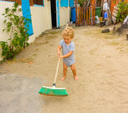 A cute toddler sweeping a yard in the caribbean Royalty Free Stock Photography