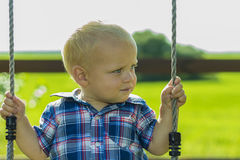 Cute toddler on a swing outdoors. Portrait of adorable baby boy playing on a child playground.  stock images