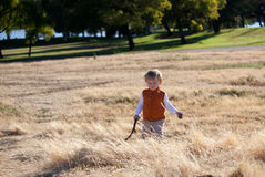 Cute toddler walking in the field of dry grass Royalty Free Stock Image