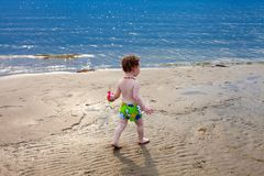 Cute toddler walks the beach. Cute toddler walks the wet sand on the beach at sunset Royalty Free Stock Images