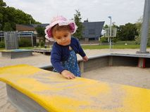 Cute toddler with pink hat and blue dress. Cute toddlerhaving fun on city playground in spring time and climbing on the yard attractions Royalty Free Stock Photos