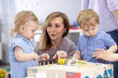 Cute toddlers babies playing with busyboard. Mother or caregiver teaching to kids in nursery. Children`s educational toys. Cute toddlers babies play with royalty free stock photo