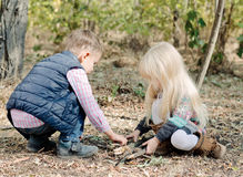 Cute Toddlers Playing with Dry Sticks on Ground. Cute White Toddlers in Autumn Outfit Playing with Dry Sticks on Forest Ground During Autumn Season stock photography