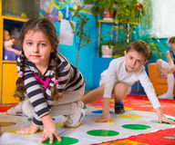 Cute toddlers playing in twister game. At kindergarten stock photography
