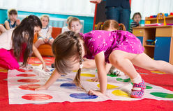 Cute toddlers playing in twister game. At kindergarten royalty free stock photo