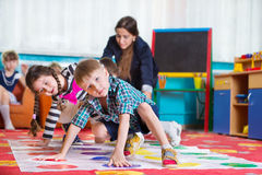 Cute toddlers playing in twister game. At kindergarten stock image