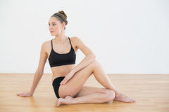 Cute toned woman stretching her body sitting on floor Royalty Free Stock Images