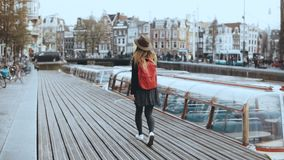 Cute tourist female walks, talks on the phone. Happy relaxed traveler walking along river boat embankment. 4K back view. Cute tourist female with red backpack stock video