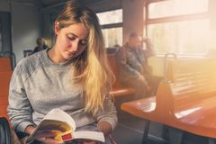 Cute tourist woman reading a book with interest near the window on the train. in warm toning stock image
