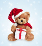 Cute toy bear with christmas gift. And santa hat on light background royalty free stock image