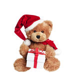 Cute toy bear with christmas gift on white. Cute toy bear with christmas gift and santa hat on white background royalty free stock photo