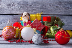 Cute toy dog sitting on gifts. Gifts for children. Stock Images