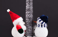 Cute toy Father Christmas and snowman under a tree. Festive scen Royalty Free Stock Image