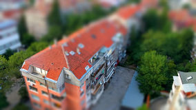 Cute toy like miniature tilt-shift effect photo of red ceramic tiling roof of a residential building illustrating poetic notion of. Toy like urban model tilt Stock Photos