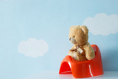 Cute toy sitting on the potty royalty free stock photos