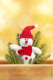 Cute toy snowman on golden background with santa h. Cute toy snowman on golden background royalty free stock photo