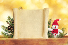 Cute toy snowman on golden background with scroll. Cute toy snowman on golden background with blanc scroll royalty free stock photos
