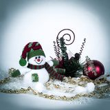 Cute toy snowman and various Christmas decorations on a white b