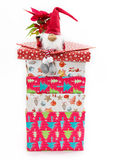 Cute toy on stack of Christmas presents. Dwarf toy (Scandinavian mythological creature tomte/ nisse) sitting on the stack of Christmas present boxes with a Stock Images