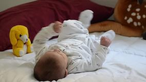 Tree months old baby boy dressed in white, on white quilt kicking with his feet and making funny faces. Cute tree months old baby boy dressed in white, on white stock footage