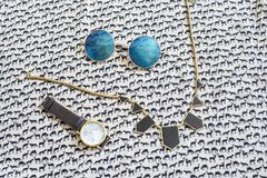 Cute trendy girlish set of necklace, round hippie glasses and fa. Shion watch laying on the unique pattern made of small deers stock image