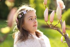 Cute tween girl with with handmade wreath on head with funny face expression looking surprisingly at magnolia tree buds. First signs of spring royalty free stock images
