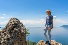 Cute tween tourist girl in hat and backpack standing on cliff top and posing against beautiful landscape of blue sky and Baikal. Lake. Hiking, travelling and stock photo