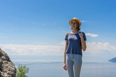 Cute tween tourist girl in hat and backpack standing on cliff top and posing against beautiful landscape of blue sky and Baikal stock image