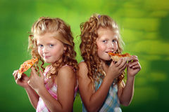 Cute twin girls eating pizza. Beautiful twin sisters eating pizza Royalty Free Stock Photo