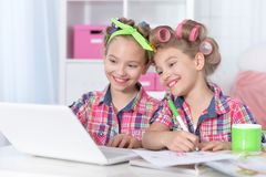 Portrait of cute twin girls in hair curlers with laptop and microphone royalty free stock image