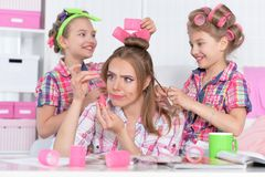 Portrait of twin girls with mother in hair curlers doing hairstyle stock image