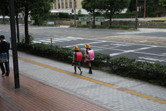 Cute Twin Japanese Student Girls. Back View of Japanese Student Girls wearing backpack on the way to school royalty free stock photo