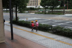 Cute Twin Japanese Student Girls. Back View of Japanese Student Girls wearing backpack on the way to school stock image