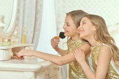 Cute twin sisters in golden dresses sitting near dressing table royalty free stock image