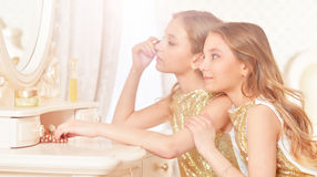 Cute twin sisters. Portrait of a cute twin sisters applying makeup while sitting at dressing table Royalty Free Stock Photos
