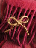 Cute twine bow hanging on colorful wool fringe. Twine bow hanging off of a fuchsia pink and magenta scarf. One hundred percent Irish wool. Vertical shot Stock Photo